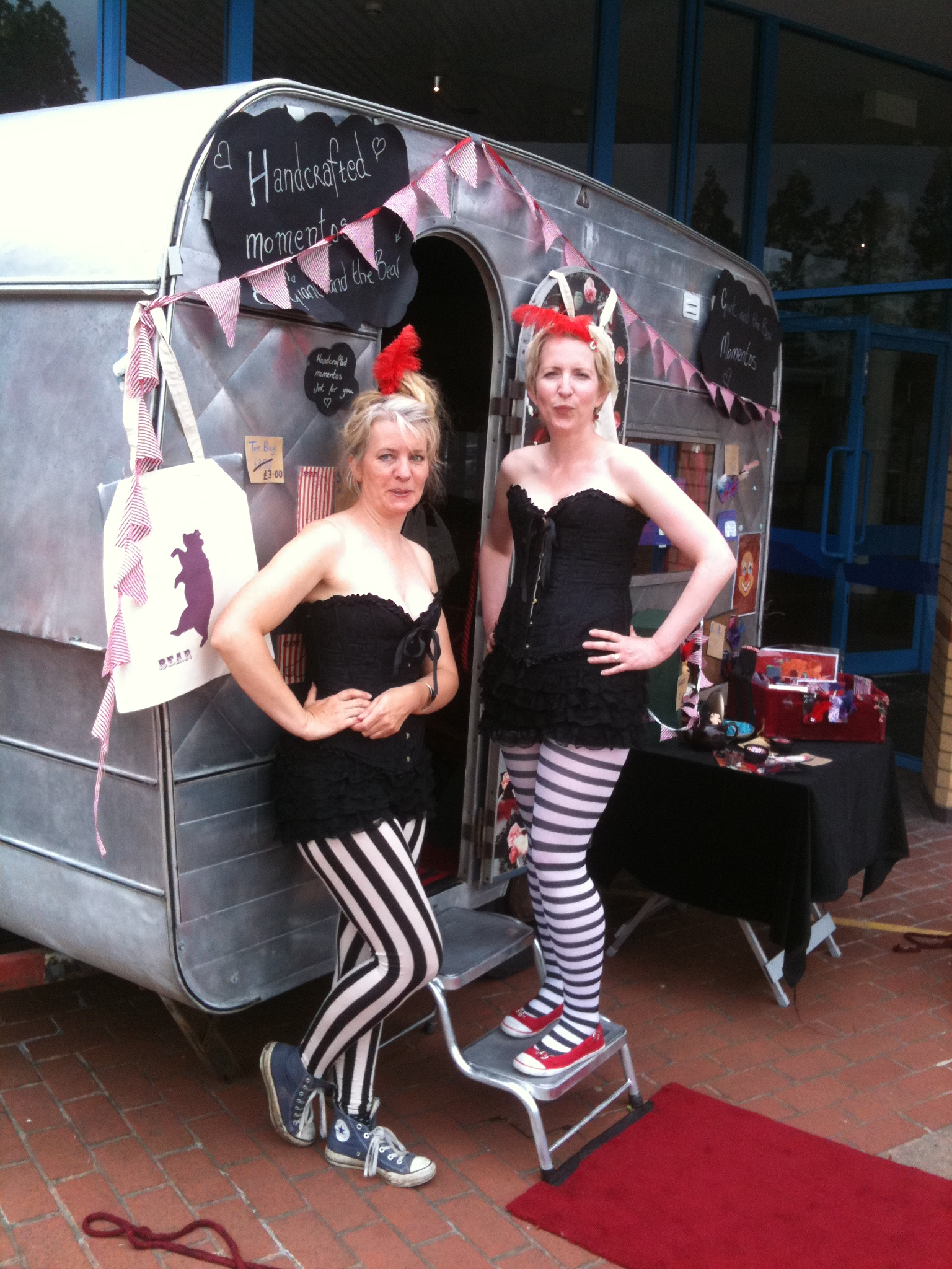 Alison McIntyre and Ginny Scholey in corsets outside Rayon Rose caravan